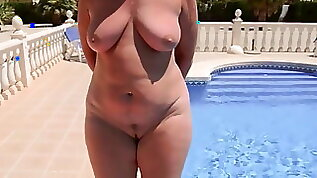 A mature woman with naked round ass walks by the pool
