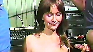 Shy slim brunette sucking two dicks in a vintage clip