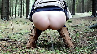 Rear view squat pee fart in the woods