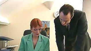 Redheaded older secretary sucks on a cock at her desk