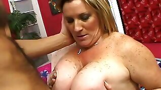 Oiled blond haired fatty stands on knees to give a kinky titjob and blowjob